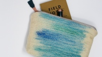 Front of handwoven zippered pouch with notebook and pen.